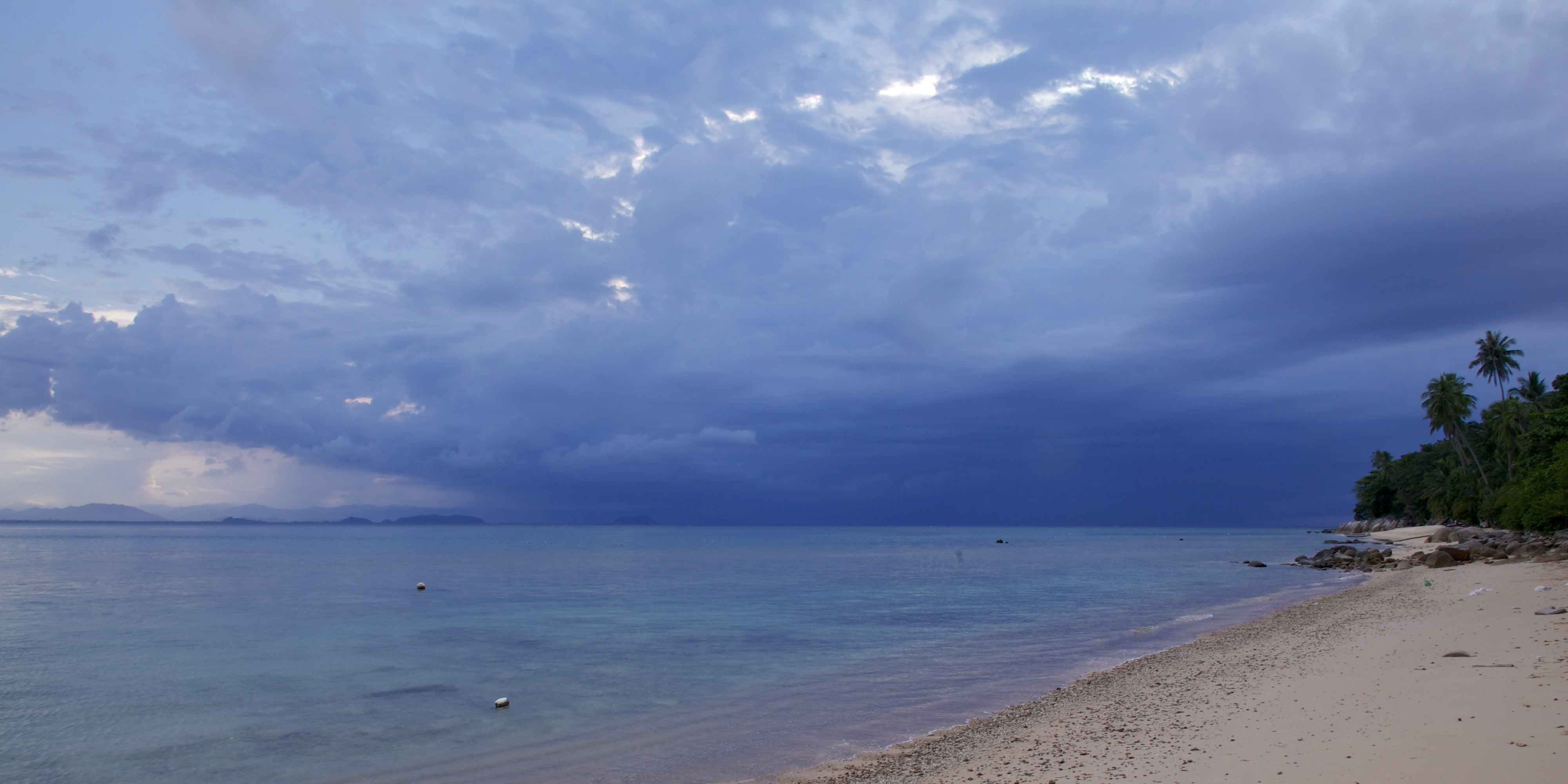 A cloud gathers over the ocean surrounding the Perhentian Islands. The annual rainy seasons give the reefs a break from tourism and help with coral reef conservation.