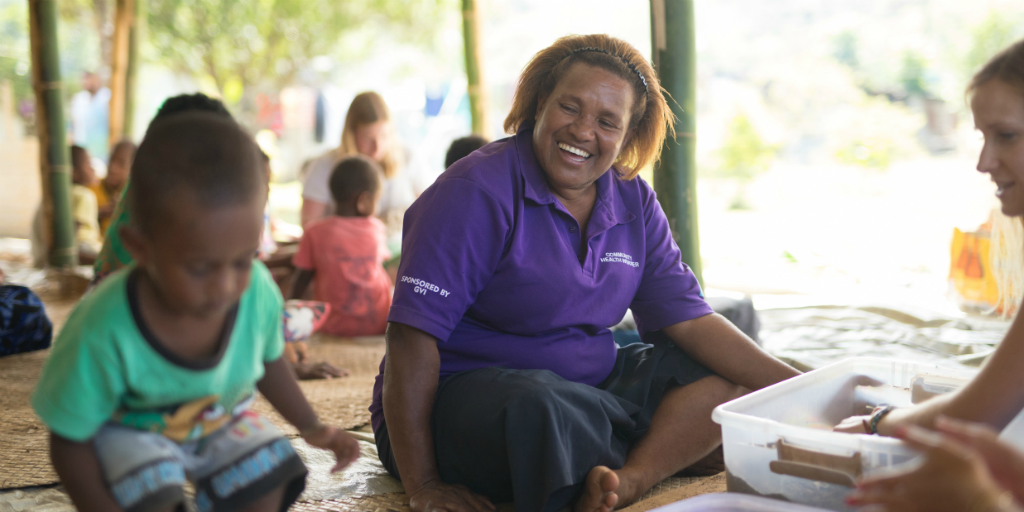 Happy local mother watching her child do an activity with a GVI volunteer