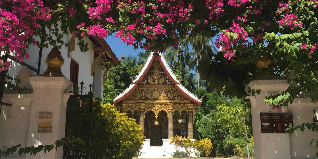 A temple beyond a bougainville archway in Thailand