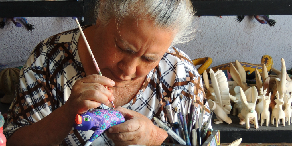 An elderley Mexican woman hand-painting a ceramic animal.