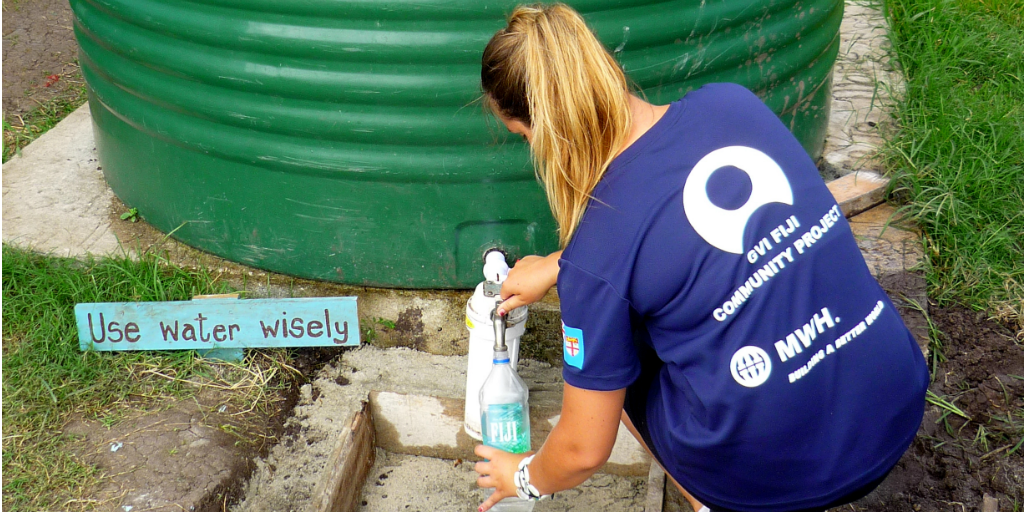 A volunteer collecting water from a rainwater collection tank in Fiji.