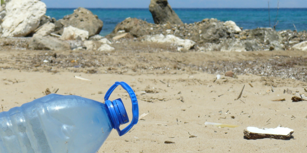 A plastic bottle lying on a beach.