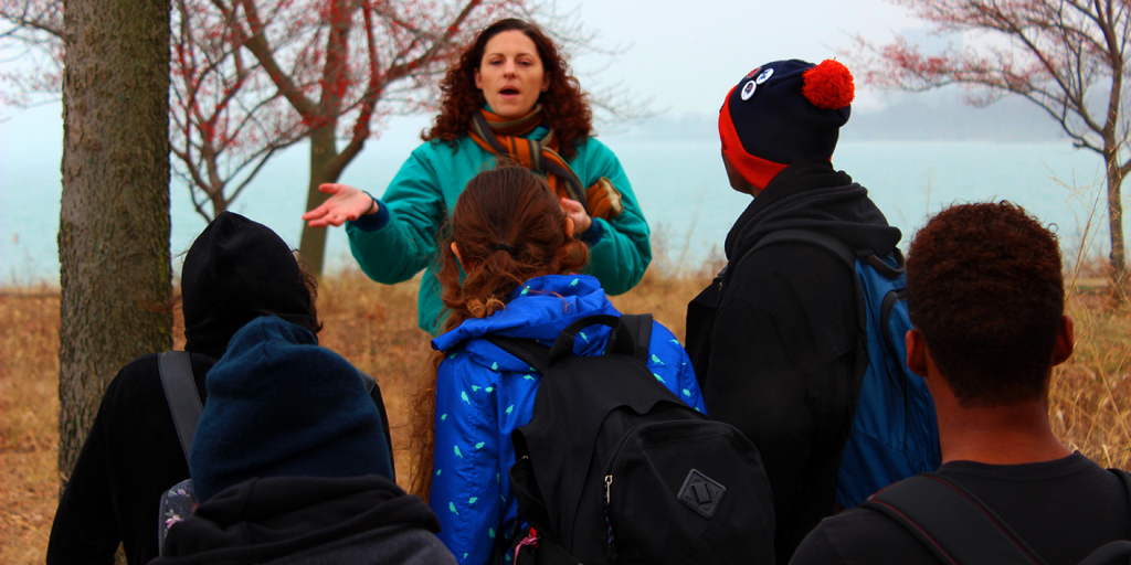 A lady speaks to the youth about an environmental restoration project.
