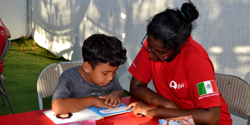 A lady helps a child read a Spanish book during a language immersion program.