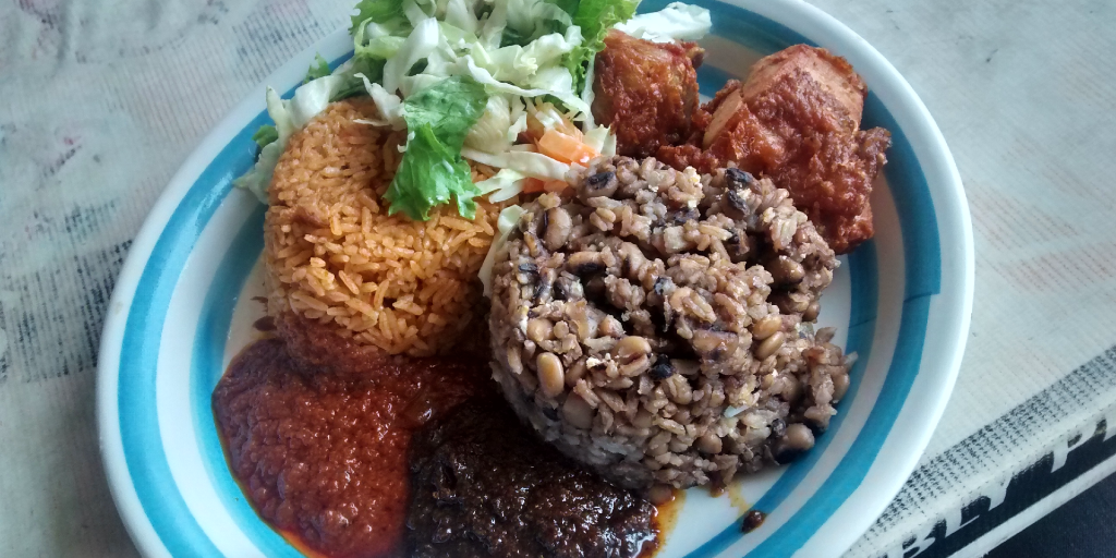 A plate filled with waakye, jollof rice and other traditional Ghanaian food.